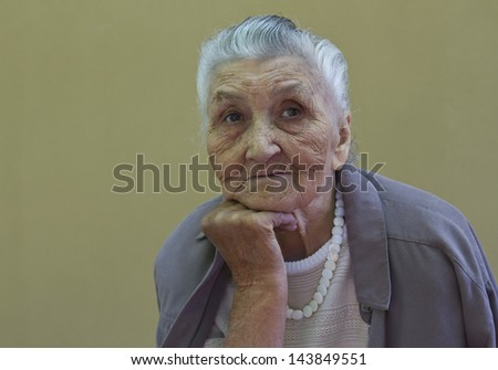 old lady's portrait in front of a light brown wall - stock photo