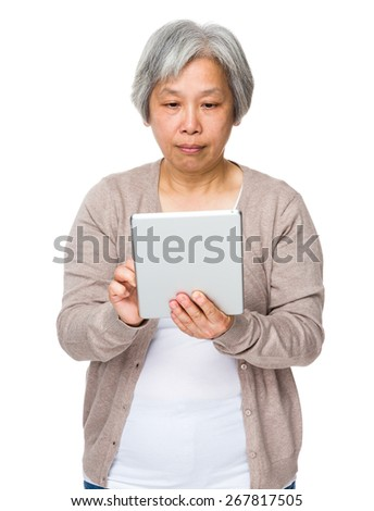 Old lady use of tablet - stock photo