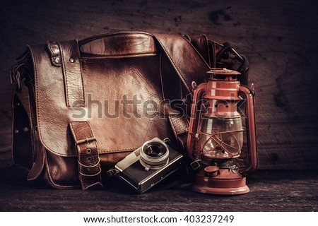 Old lamp and retro camera with leather bag on wooden background, vintage style - stock photo