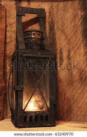Old lamp with lighted candle on wooden background - stock photo