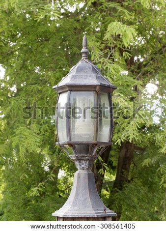 Old lamps on green tree background - stock photo