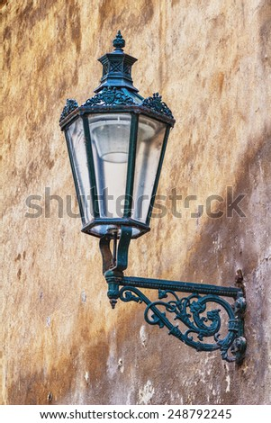 Old lantern on dirty wall - stock photo