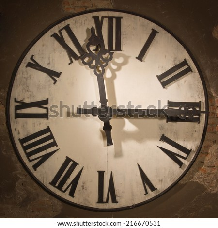 Old large clock face hanging on a wall  - stock photo