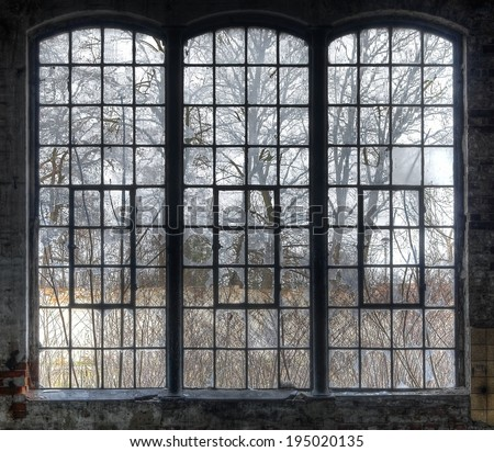 Old large window with broken panes in a deserted hall - stock photo