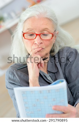 Old last doing a crossword - stock photo