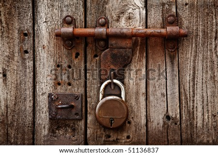 Old latch with padlock on gatees