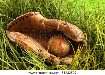 Old leather baseball glove with ball in the grass - stock photo