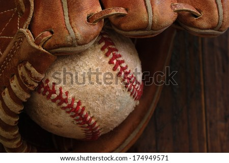 Old leather baseball glove with weathered baseball on wood background.  Highly detailed closeup taken in soft side lighting to emphasize stitching and texture.  Low key still life with shallow dof.
