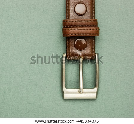 Old leather belt with a buckle on a green background - stock photo