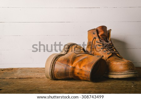 Old leather boot traditional leather style on wooden background with filter vintage style effect - stock photo