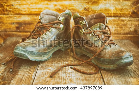 Old leather boots. Boots on a wooden background. Vintage toning - stock photo