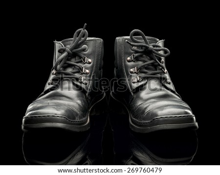 Old leather boots of black color are isolated on black