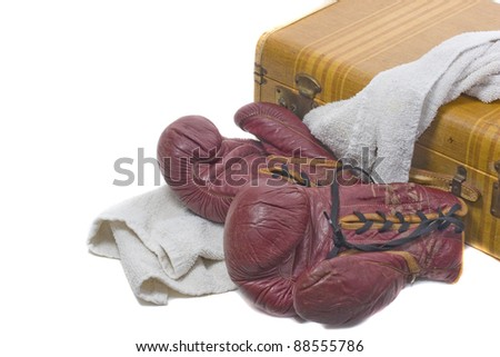 old leather boxing gloves on a towel and old suite case - throwing in the towel - stock photo