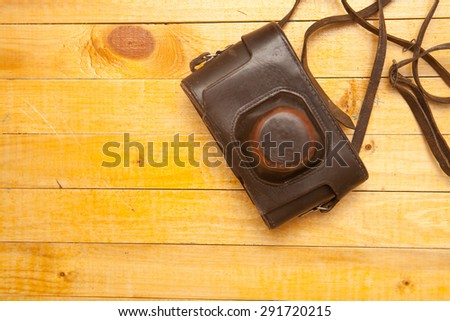 old leather carrying case for the camera on a wooden background