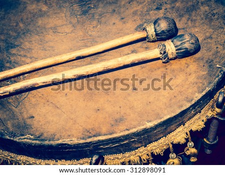 Old leather drum and drumsticks - membrane musical instrument. Ancient ethnic music on a folk festival. Timpani or kettledrums - old musical instruments in percussion family of classical orchestra. - stock photo