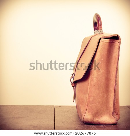 Old leather school bag on desk retro style filtered photo - stock photo