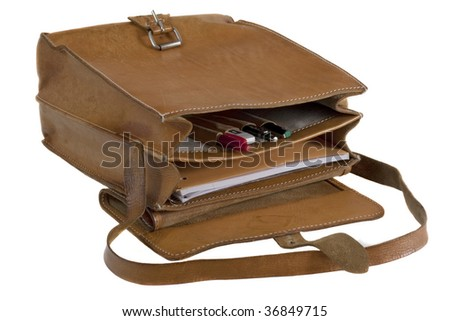 old leather school bag with scratches and stains - opened showing pens and notebook, isolated on white