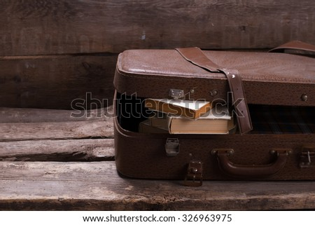 Old leather suitcase with books on vintage wooden background.