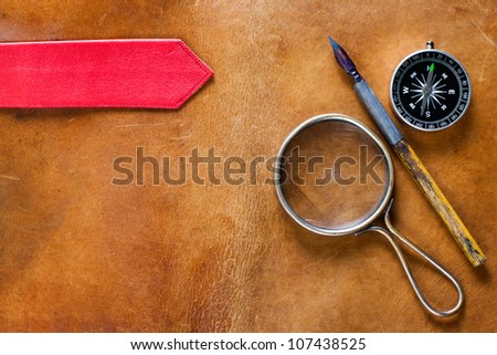 Old leather with magnifying glass, compass and ink pen - stock photo