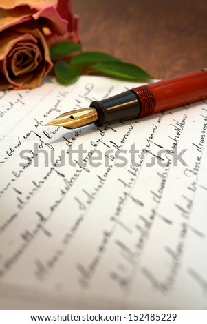 Old letter on a desk with a fountain pen on top - stock photo