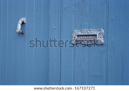 Old letter postbox and  metal knocker on blue wooden door in France - stock photo