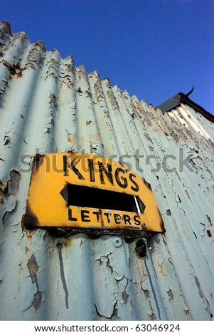 Old letter-slot in rusty fence - stock photo