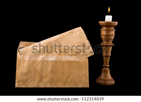 old letters and candle on a black background - stock photo
