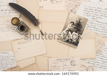 old letters, vintage postcards and antique feather pen. nostalgic sentimental background with retro christmas postcard - stock photo
