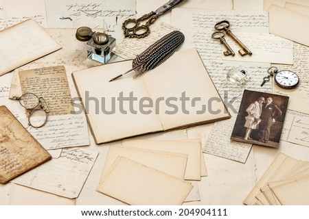 old letters, vintage postcards and antique feather pen. nostalgic sentimental background with retro picture of young couple - stock photo
