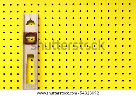 Old level hangs from a hook on yellow pegboard.