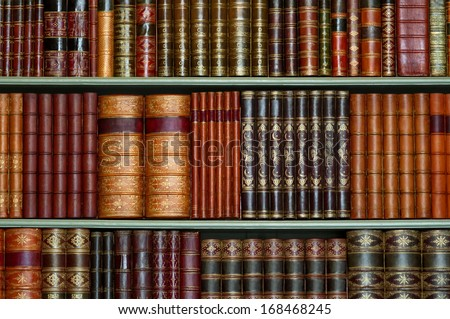 Old library of vintage hard cover books on shelves - stock photo