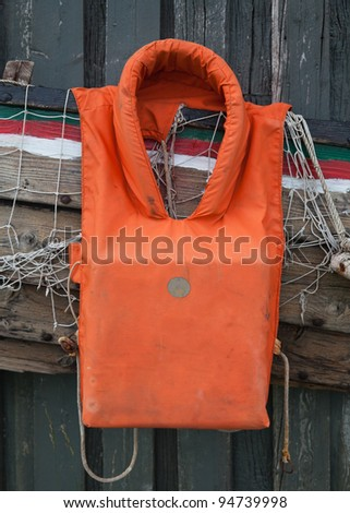 old life jacket on the background of a fishing net and boat wreckage