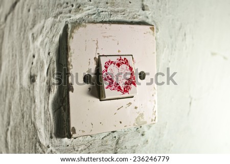 Old light switch with red paint love heart on old cracked green wall - stock photo