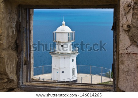 Old lighthouse against blue sky in Crimea, Ukraine - stock photo