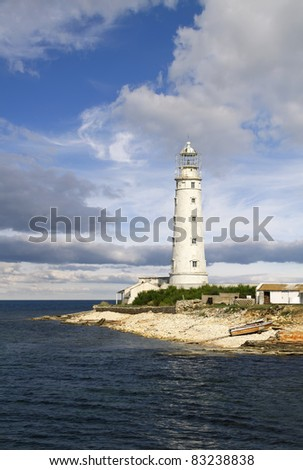 old lighthouse at a coastline - stock photo