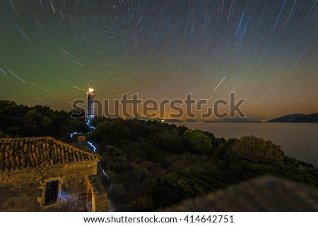 Old lighthouse in Greece with rotating stars - stock photo