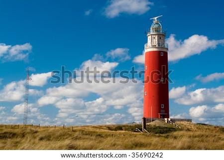 Old lighthouse on a seashore. Daytime - stock photo