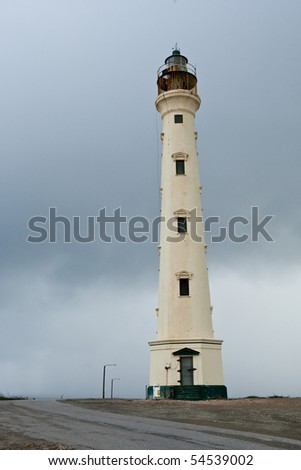 Old lighthouse standing against cloudy sky.