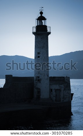 Old lighthouse tower silhouette on the coast of Mediterranean Sea, no light. Blue toned, stylized night photo - stock photo