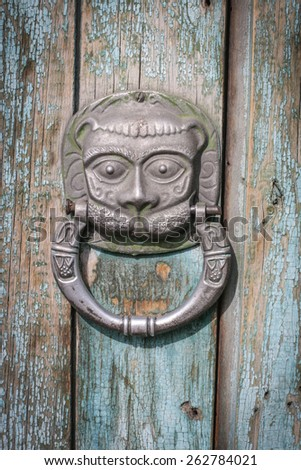 old  lion shaped door knocker on an antique wooden door - stock photo