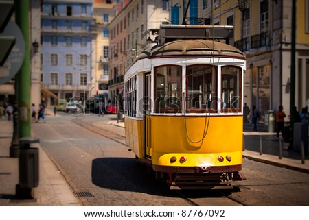 Old Lisbon yellow tram on the street. Focus on the tram - stock photo