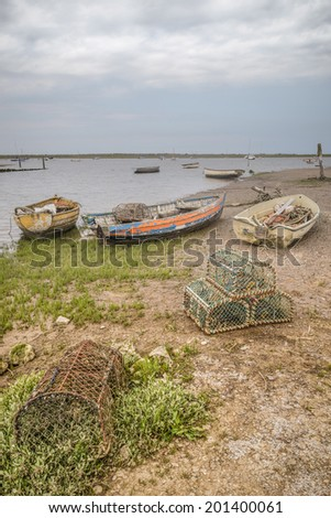 Old lobster pots and fishing boats line the old dock at Brancaster Staithe - stock photo
