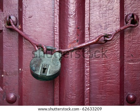Old Lock Key on Close Red Wood Door - stock photo
