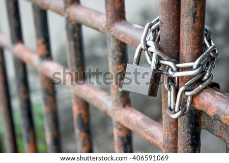 Old lock pad locked on fence with chain. - stock photo