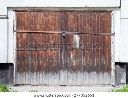 Old locked wooden gate in white concrete wall of an ordinary living house - stock photo