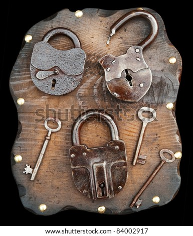 Old locks and keys on wooden plank isolated on black. Clipping path included. - stock photo