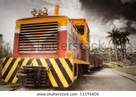 Old locomotive of railway in rural field under dramatic sky. - stock photo