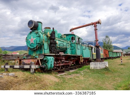 Old locomotive with wagons standing at a gas station - stock photo