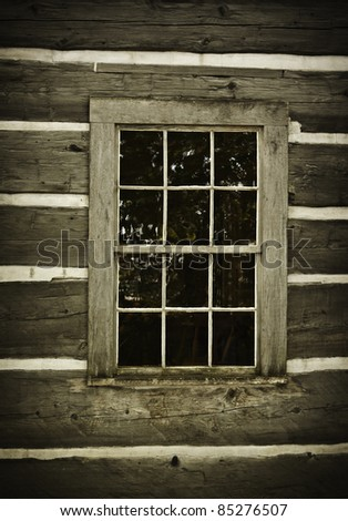 Old log cabin wall and window. Rustic and abandoned. - stock photo