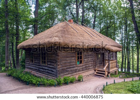 old log house with one window, surrounded by trees in the summer - stock photo
